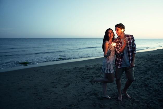 Casal romântico com sparkler em uma praia do por do sol