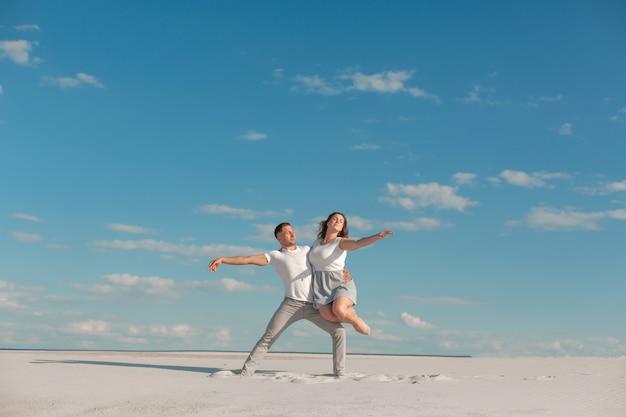Casal romântico dançando no deserto de areia com céu azul