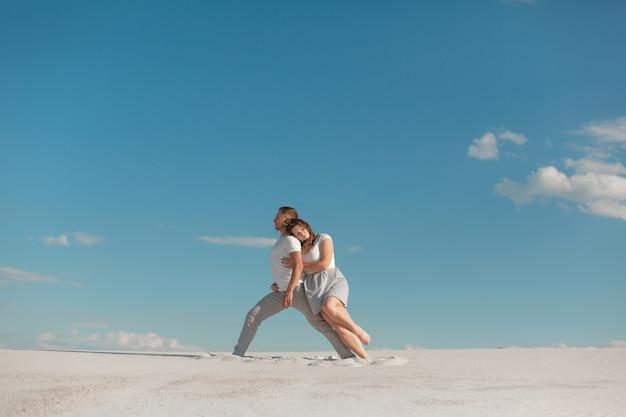 Casal romântico dançando no deserto de areia no céu azul