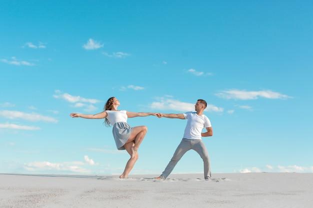 Casal romântico dançando no deserto de areia