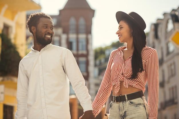 Casal romântico de jovens adultos sorrindo um para o outro enquanto caminhava