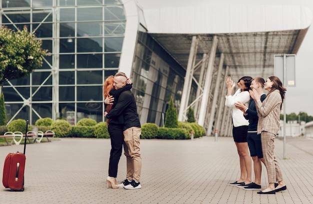 Casal romântico em pé perto do aeroporto com uma mala