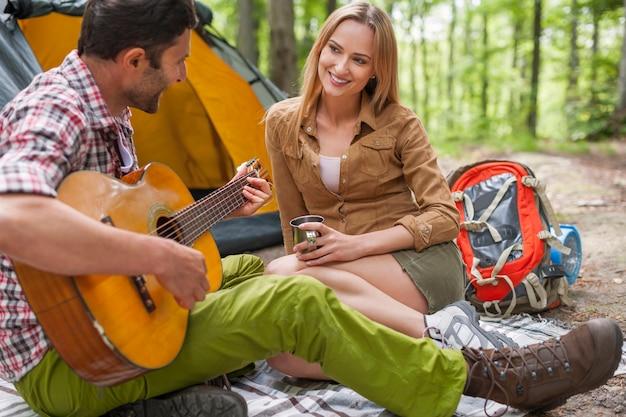 Casal romântico em um acampamento. homem tocando violão.