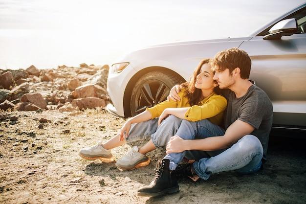 Casal romântico está perto de um muscle car na praia. o belo barbudo e uma jovem atraente têm uma história de amor.