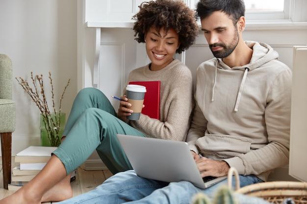 Casal romântico está sentado no chão, concentrado no laptop, assiste a filmes interessantes online, toma um café aromático, está de bom humor, aproveita a conexão sem fio à internet, tem tempo livre