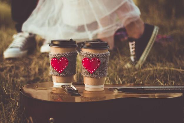 Casal romântico fazendo piquenique ao pôr do sol xícara de café manga de malha aconchegante com coração de feltro