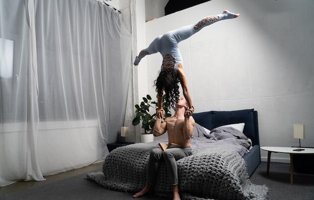 Casal romântico fazendo truque acrobático no quarto.