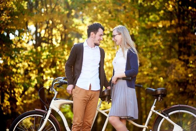 Casal romântico feliz ativo, homem barbudo e mulher atraente juntos na bicicleta dupla em tandem ao ar livre no outono park ou floresta