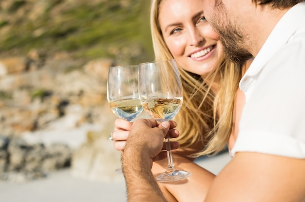 Casal romântico feliz tomando uma taça de vinho branco na praia
