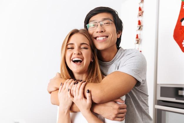 Casal romântico, homem e mulher, em pé na cozinha bem iluminada e se abraçando