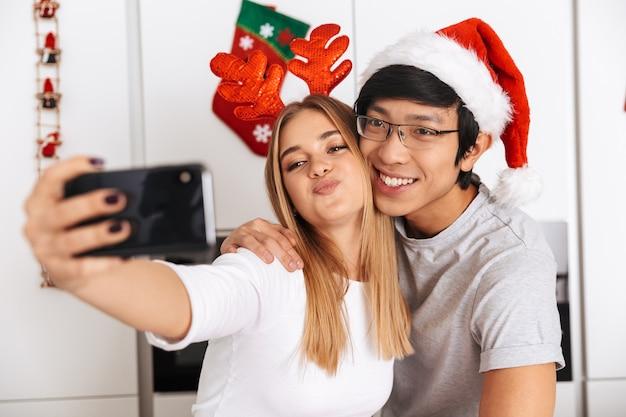 Casal romântico, homem e mulher vestindo roupas de natal, em pé na cozinha bem iluminada e tirando uma foto de selfie no celular