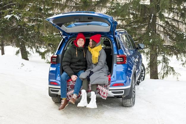 Casal romântico jovem hippie se abraçando enquanto está sentado no porta-malas. amor dia dos namorados