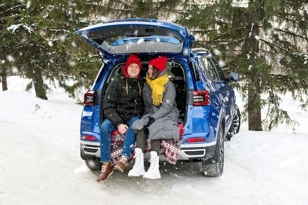 Casal romântico jovem hippie se abraçando enquanto está sentado no porta-malas do carro sob a neve caindo. celebração do dia dos namorados