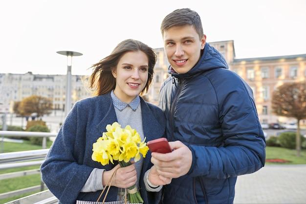 Casal romântico, jovem homem e mulher com buquê de flores amarelas