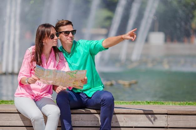 Casal romântico junto com o mapa da cidade ao ar livre. felizes amantes apreciando a paisagem urbana com monumentos famosos.