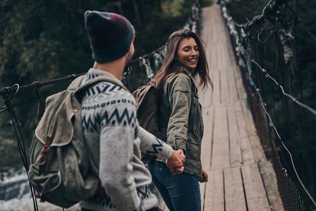 Casal romantico. lindo casal jovem de mãos dadas enquanto caminha na ponte pênsil