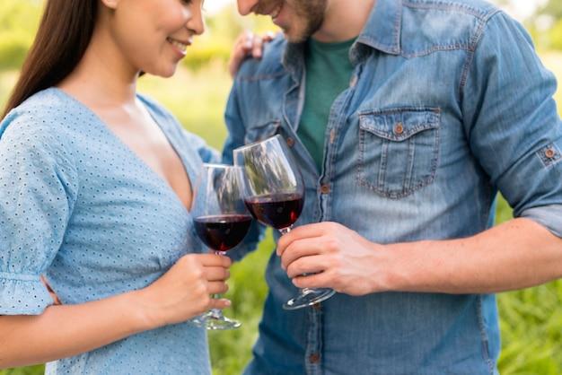 Casal romântico multiétnico tinindo copos de vinho