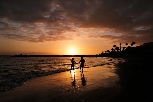 Casal romântico na praia em um pôr do sol colorido no fundo. um cara e uma garota ao pôr do sol na ilha de tenerife.
