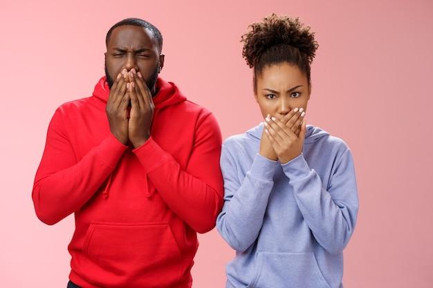 Casal romântico namorado afro-americano se sente mal depois de comer o jantar restaurante imprensa palmas das mãos boca franzindo a testa quer vomitar vômito, em pé enojado fundo rosa chocado