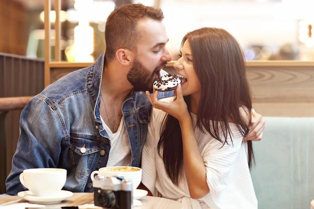 Casal romântico namorando em um café e comendo rosquinha