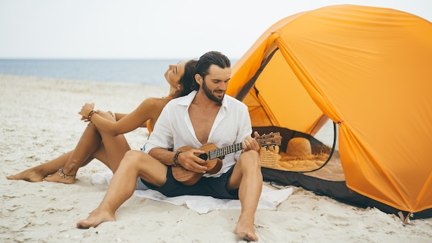 Casal romântico perto de uma barraca na praia Foto Premium