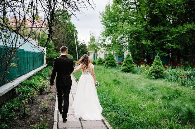 Casal romântico recém-casados, noiva e noivo está voltando em uma trilha em um parque verde. momento de casamento feliz e alegre.