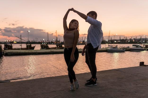 Casal romântico saindo ao pôr do sol no porto