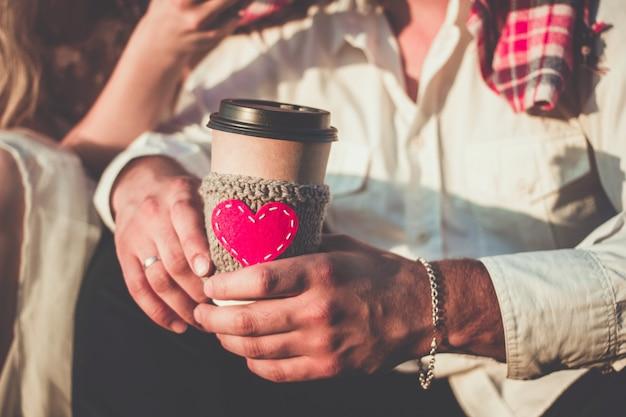 Casal romântico se abraçando enquanto faz piquenique xícara de café manga de malha aconchegante com coração de feltro vermelho