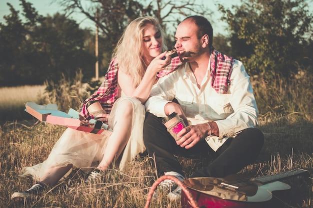Casal romântico se abraçando enquanto faz um piquenique à luz do sol