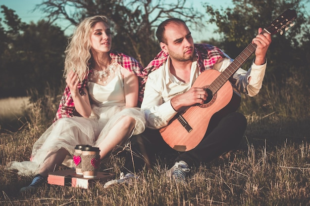Casal romântico se abraçando enquanto faz um piquenique na luz do sol. homem com guitarra e uma jovem bonita