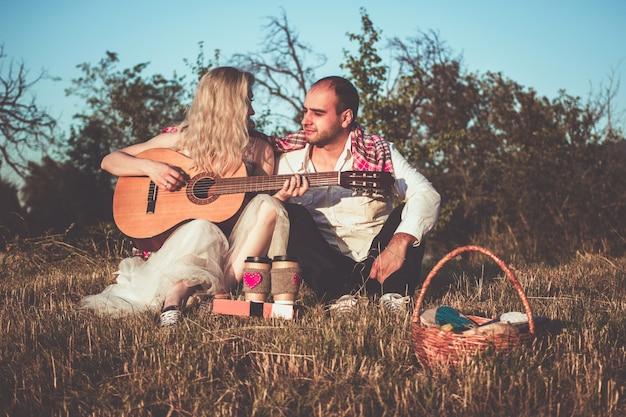 Casal romântico se abraçando enquanto faz um piquenique na luz do sol. homem tocando violão