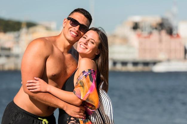 Casal romântico se abraçando na praia com espaço de cópia