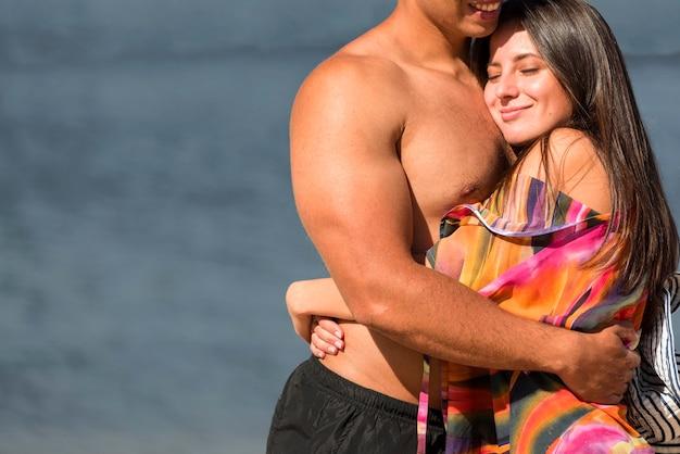 Casal romântico se abraçando na praia