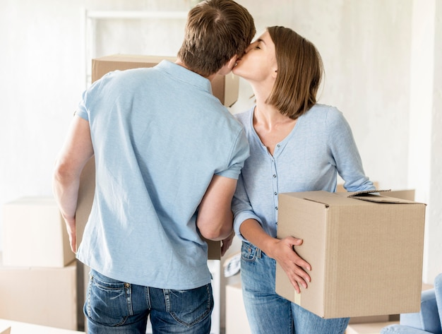 Casal romântico se beijando enquanto faz as malas para ir embora