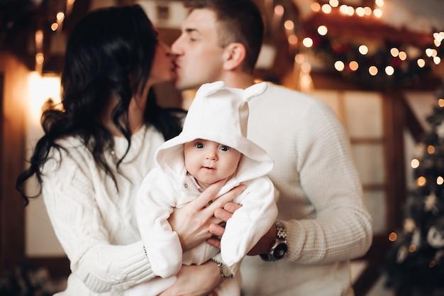 Casal romântico segurando seu lindo bebê com capuz e sorrindo para a frente