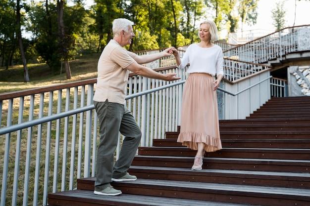 Casal romântico sênior posando juntos ao ar livre em degraus
