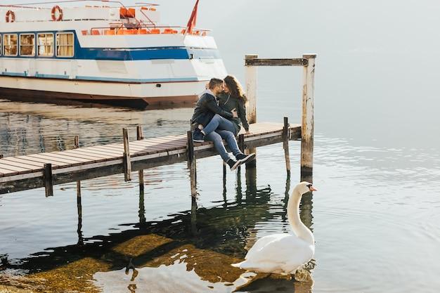 Casal romântico sentado no cais de madeira às margens do lago lugano, suíça em dia ensolarado.