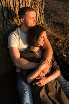 Casal romântico sentado perto de uma árvore