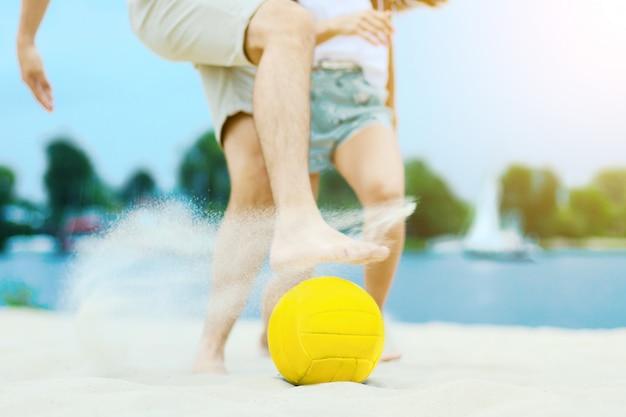 Casal romântico sorridente ativo feliz jogando jogo de futebol na areia de faia