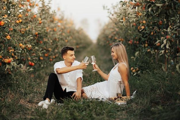Casal romântico tilintando de copos com vinho branco enquanto está sentado no piquenique na natureza.