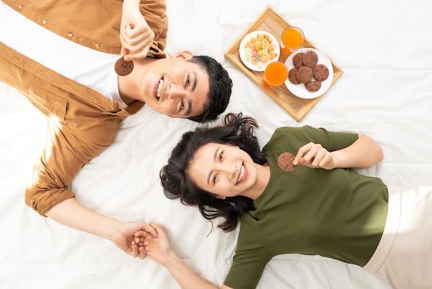 Casal romântico tomando café da manhã deitado na cama em casa