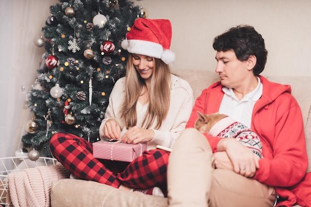 Casal romântico trocando presentes perto da árvore de natal decorada