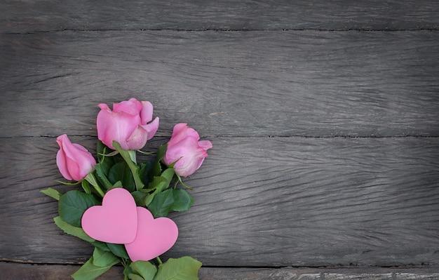 Casal rosa de corações e rosas cor de rosa em fundo de madeira