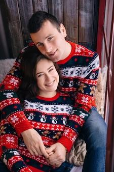 Casal se abraça no parapeito da janela e olhando para a câmera. suéteres elegantes de inverno.
