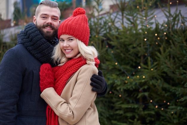 Casal se abraçando ao lado da árvore de natal