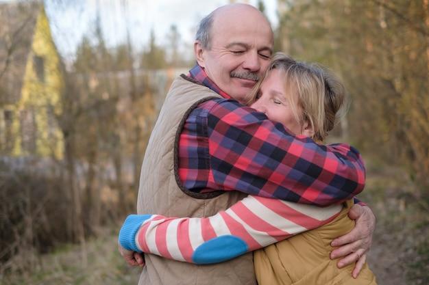 Casal se abraçando caminhando ao ar livre no outono