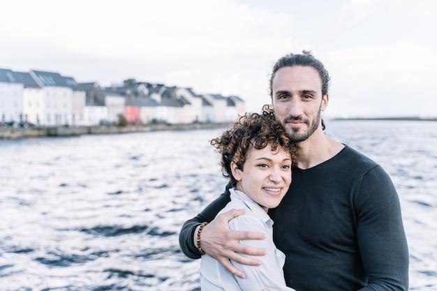 Casal se abraçando com o mar fora de foco