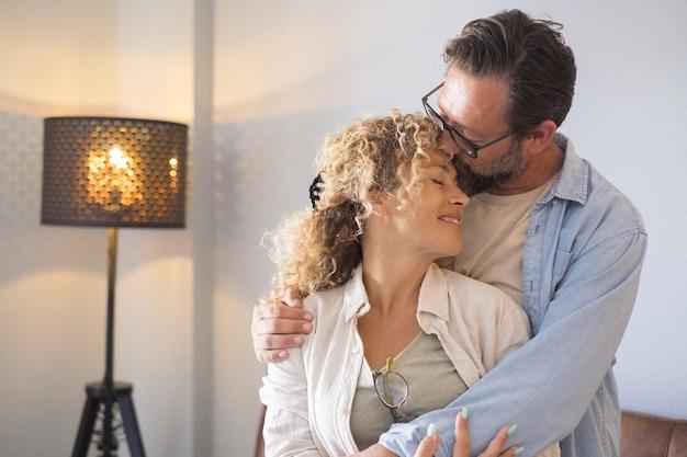 Casal se abraçando e namorando em pé na sala de estar em casa. marido beijando a testa da esposa com carinho. casal afetuoso passando momentos de lazer juntos em casa