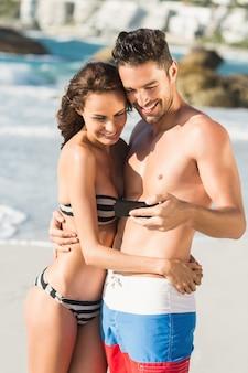 Casal se abraçando e olhando para smartphone