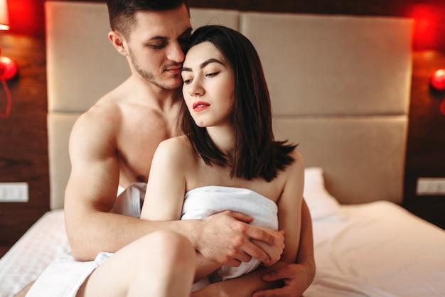 Casal se abraçando em uma grande cama branca após intimidade
